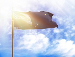 National flag of State of Alaska on a flagpole in front of blue sky