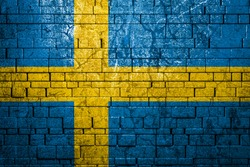 National flag of Sweden on brick  wall background.The concept of national pride and symbol of the country. Flag  banner on  stone texture background.