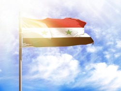 National flag of Syria on a flagpole in front of blue sky