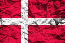 National flag of the Kingdom of Denmark on crumpled paper. Flag printed on a sheet. Flag image for design on flyers, advertising.