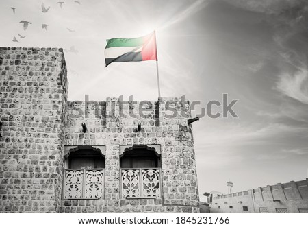 National flag of UAE flying on an old, ancient Arabic house. Black and white, archival photo of Emirati house with color national flag.