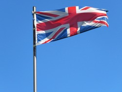 National flag of United Kingdom on a flagpole in front of blue sky