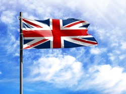 National flag of United Kingdom on a flagpole in front of blue sky.