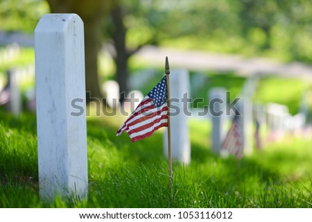 National flags ant headstones in Arlington National cemetery during Memorial Weekend - Washington DC, United States - Shutterstock ID 1053116012