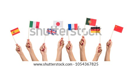 National flags of Germany, England, Italia, Japan, China Spain, France, Portugal in hands. Language studying concept on white background #1054367825