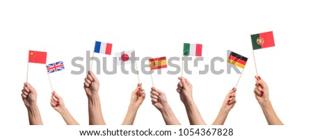 National flags of Germany, England, Italia, Japan, China Spain, France, Portugal in hands. Language studying concept on white background #1054367828