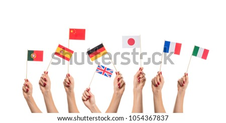 National flags of Germany, England, Italia, Japan, China Spain, France, Portugal in hands. Language studying concept on white background #1054367837