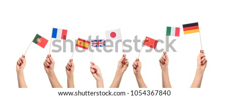 National flags of Germany, England, Italia, Japan, China Spain, France, Portugal in hands. Language studying concept on white background #1054367840