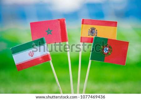 National Flags of Portugal, Spain, Morocco, IR Iran. Flags on green grass on football stadium. Group B draw  #1077469436