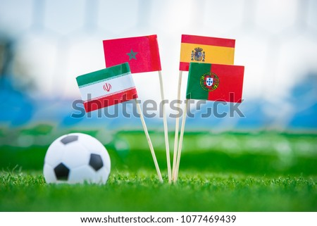 National Flags of Portugal, Spain, Morocco, IR Iran. Flags on green grass on football stadium. Group B draw #1077469439