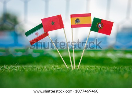 National Flags of Portugal, Spain, Morocco, IR Iran. Flags on green grass on football stadium. Group B  #1077469460