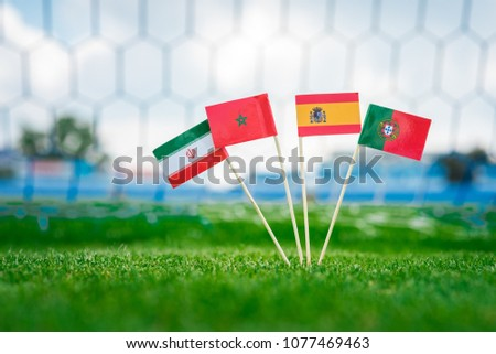 National Flags of Portugal, Spain, Morocco, IR Iran. Flags on green grass on football stadium. Group B #1077469463