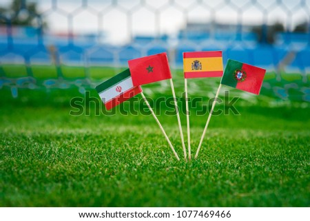 National Flags of Portugal, Spain, Morocco, IR Iran. Flags on green grass on football stadium. Group B  #1077469466