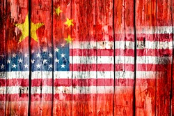 National flags of the People's Republic of China and the United States of America painted on an old wooden door with flakey paint