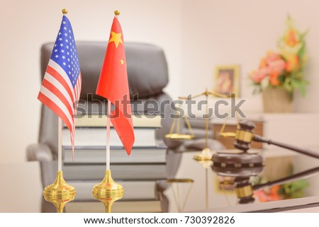 National flags of USA and China put on a table with books, gavel and a balance scale of justice behind. A symbol of cooperation between two nations, Washington and Beijing i.e. business dialogue, etc. #730392826