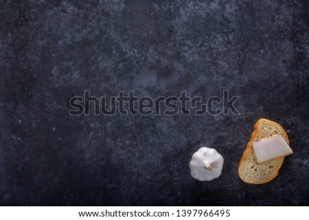 National food concept. Piece of bread and a piece of bacon on a gray stone background, flat lay with space for text