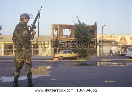 National Guardsman patrolling in front of burned business after 1992 riots, South Central Los Angeles, California