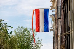 National holiday King's Day or Koningsdag in Dutch, Due to Coronavirus disease (COVID-19) scourge, Celebrations will not take place this year, Netherlands flag and orange flag hanging outside building