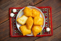 National Kazakh pastries baursaki and kurt in a plate on a wooden background