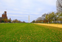 National Mall in autumn with the Washington Monument at distance in Washington DC, USA. The National Mall landscape with empty benches and historic buildings on both sides under cloudy skies.
