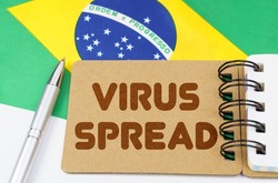 National medicine concept. On the flag of Brazil lies a notebook with the inscription - VIRUS SPREAD