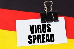 National medicine concept. On the flag of Germany lies a notebook with the inscription - VIRUS SPREAD