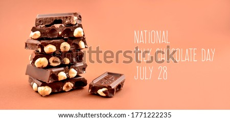 National Milk Chocolate Day stock images. Pile of chocolate with nuts images. Chocolate isolated on a brown background. Milk Chocolate Day Poster, July 28. Important day