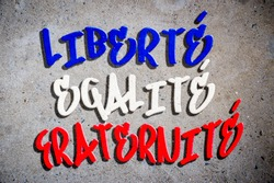 National motto of France (English translation: Liberty, Equality, Fraternity) written in French blue, white, and red tricolor in graffiti text on textured concrete wall
