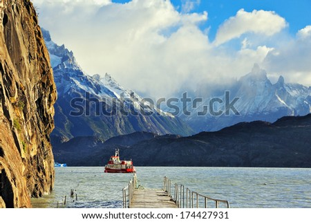 National Park Torres del Paine, Chile. Pier on Lake Grey. Red tourist ship sails to the dock. In the mountains around the lake are piled clouds. Summer sun illuminates the lake.