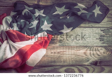 National Patriotic symbols. American flag on an old wooden background.The concept of patriotism and celebration