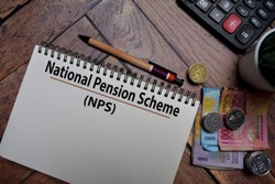 National Pension Scheme (NPS) write on a book isolated on wooden table.