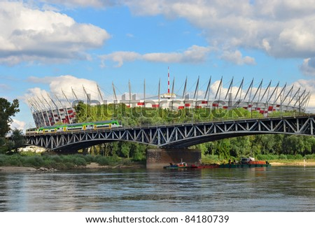 National Stadium in Warsaw built for football competition Euro 2012. View over Vistula river. Train on the bridge.