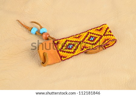 Native American bracelet with burgundy, orange, yellow and turquoise beads in geometric design on rawhide leather and displayed on buckskin background.