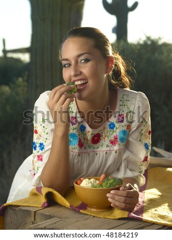 Native American brunette model leaning on wooden table eating healthy vegetables in front of giant saguaro cactus on Arizona ranch landscape.