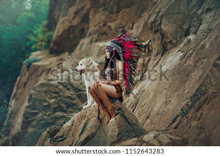 Native American Indian woman. The huntress sits on the rock with the wolf and looks into the distance. Dog Alaskan Malamute. On the girl beads, leather skirt, ethnic jewelry.