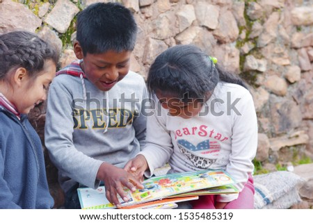 Native american kids reading a  book.