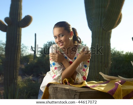 Native American model leaning on weathered table and horse blanket outdoors between two giant saguaro cactus in Arizona landscape.