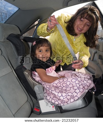 Native American woman placing her daughter in a child safety seat and fastening her seat belt