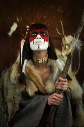 Native american woman portrait with painted face. Young beautiful woman in native american costume with wolf fur and war mask on her face holding a medecine staff