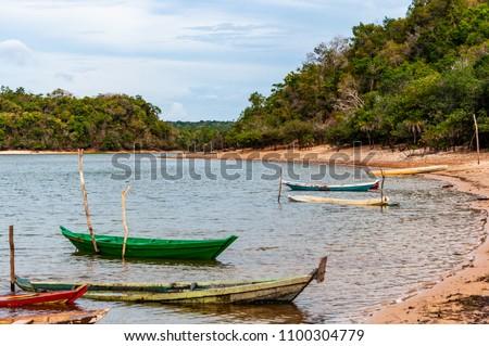 Native Brazilian fisherman canoe floating in Tapajos river, on Amazon