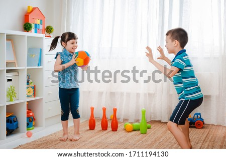 native children boy and a girl play in a children's game room, throwing ball. concept of interaction siblings , communication, mutual play, quarantine, self-isolation home, brother sister.