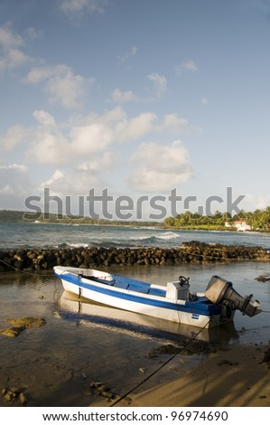 native panga fishing boat Caribbean Sea with coconut palm trees modern hotel in background Big Corn Island Nicaragua Central America