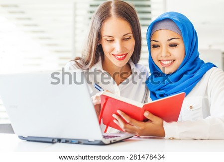Native speaker teaching a muslim asian girl in a light classroom in college