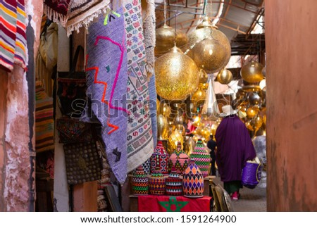 native woman walking through the souk of Marrakech between lamps lamps and other articles