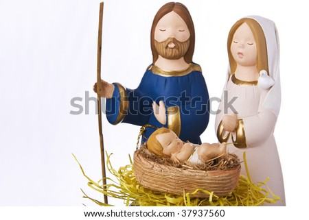 Nativity scene: Jesus, Mary and Joseph at the manger. Focus on baby Jesus, soft focus on Mary and joseph.