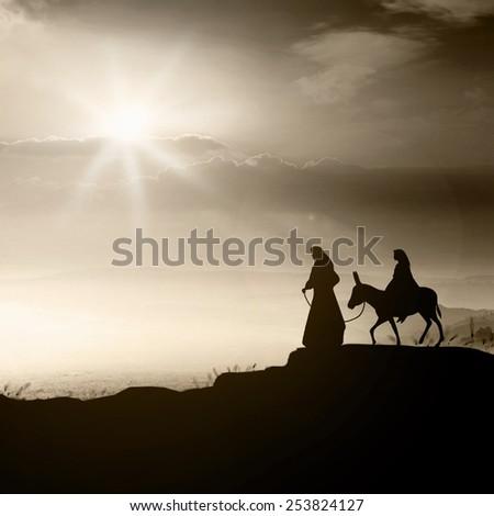 Nativity story concept: Joseph, Mary and baby Jesus with donkey on Bethlehem city of Christmas eve background.