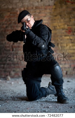 NATO soldier with M4 rifle on the brick wall background.