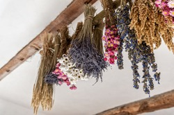 Natural and colorful dried flower bouquets with bunches of grains hung upside down from a barn ceiling.