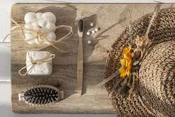 natural and no waste objects for body care on chopping board: soap, solid shampoo, brush, tooth brush, toothpaste tablets and straw hat