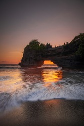 Natural arch. Batu Bolong temple on the rock during sunset. Seascape background. Motion milky waves on black sand beach. Copy space. Vertical layout. Tanah Lot, Bali, Indonesia